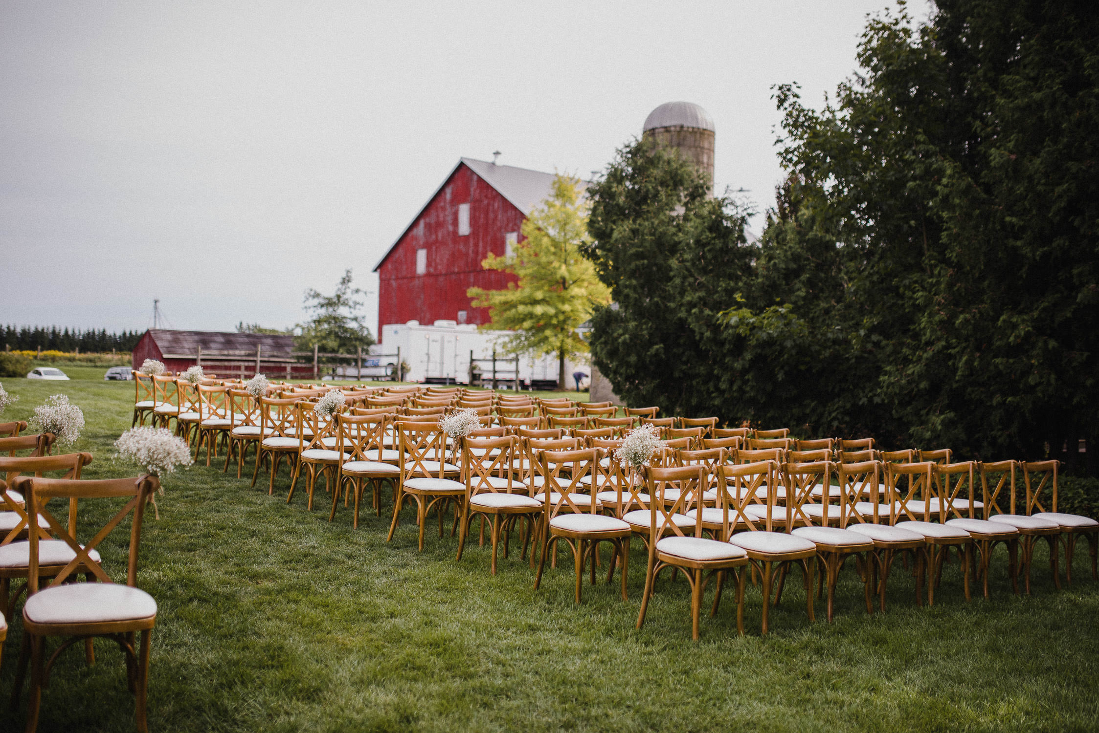 Chairs line the green grass behind the red barn before the wedding ceremony at Cambium Farm.