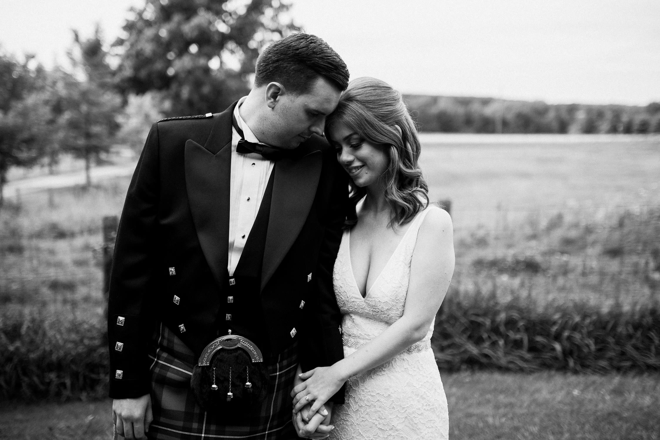 Black and white portrait of the bride and groom embracing before their wedding ceremony at Cambium Farm.