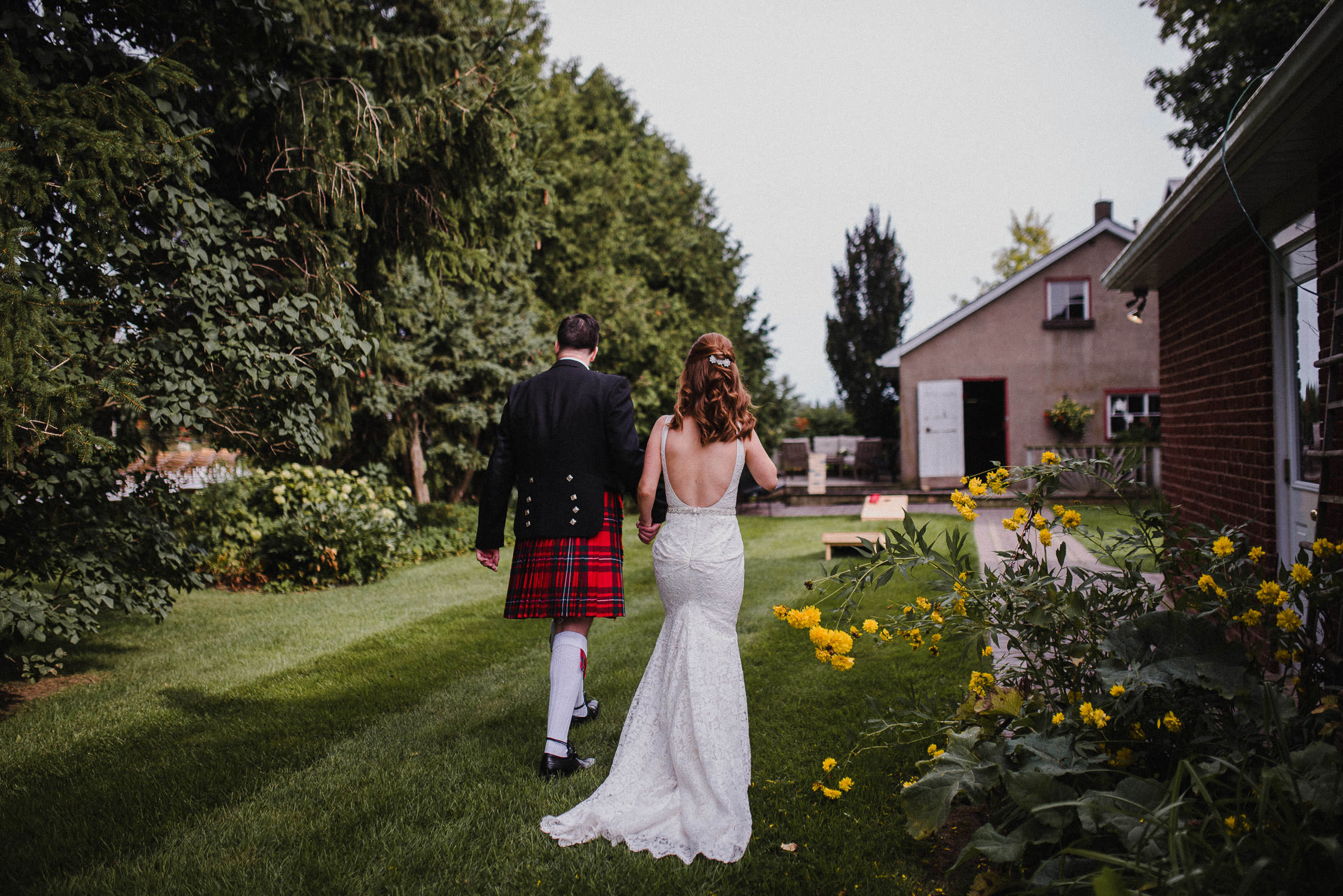 The bride and groom walk along the grass hand-in-hand before their wedding ceremony at Cambium Farm.