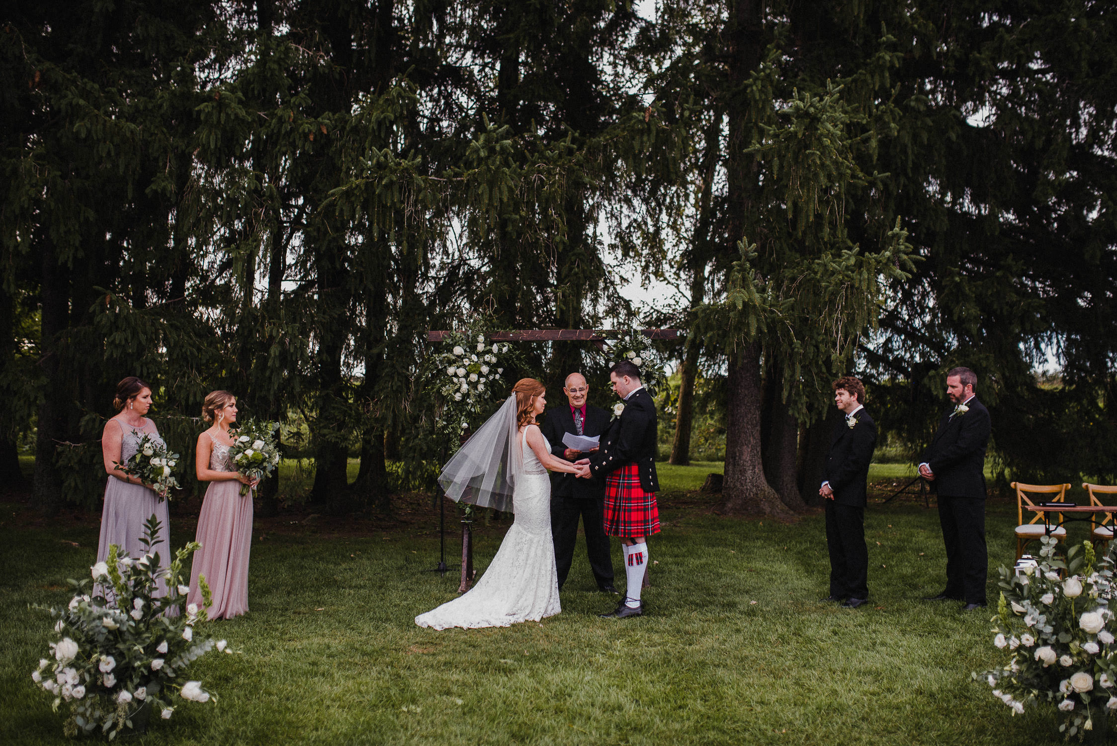 The bride and groom stand hand-in-hand at the alter during their wedding ceremony at Cambium Farm.