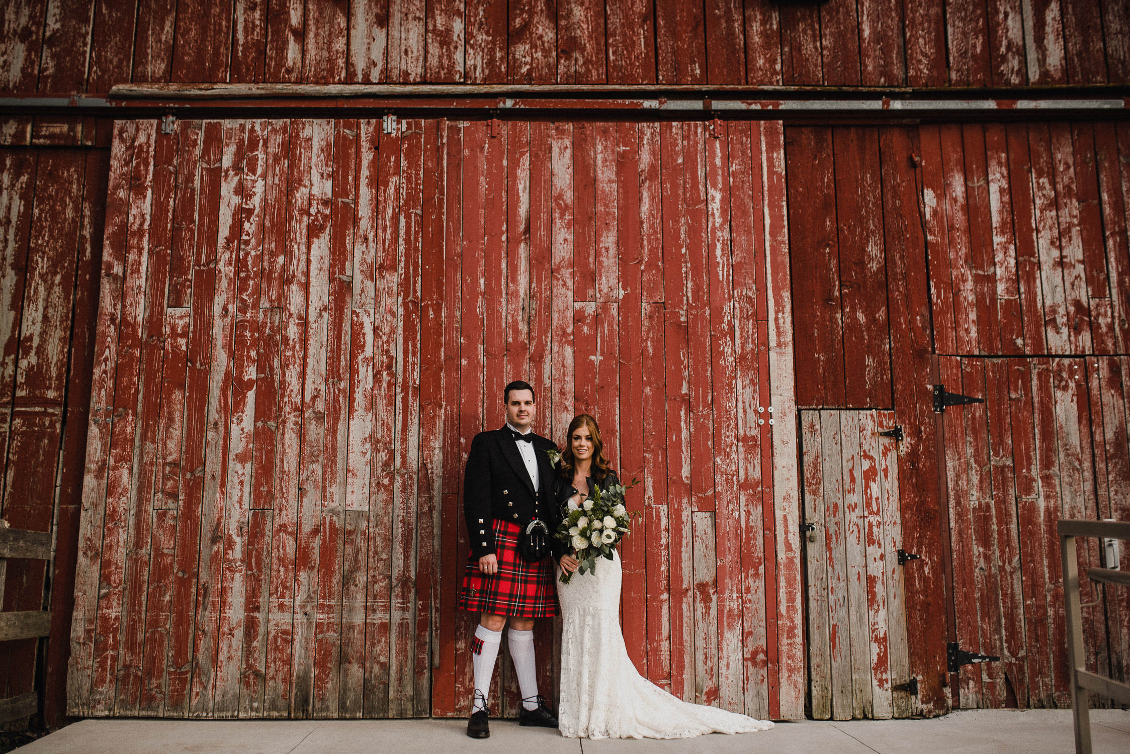 Portrait of the bride and groom in front of a red barn after their wedding ceremony at Cambium Farm.