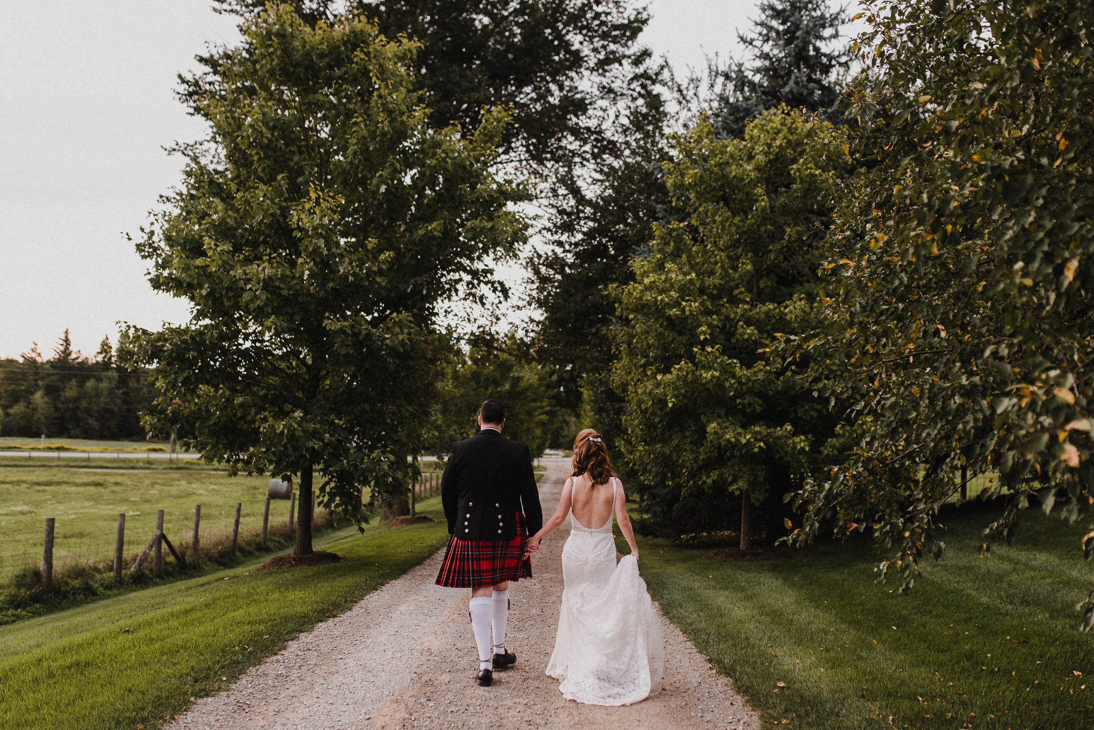 The bride and groom walk down a tree-lined path on the farm after their wedding ceremony at Cambium Farm.