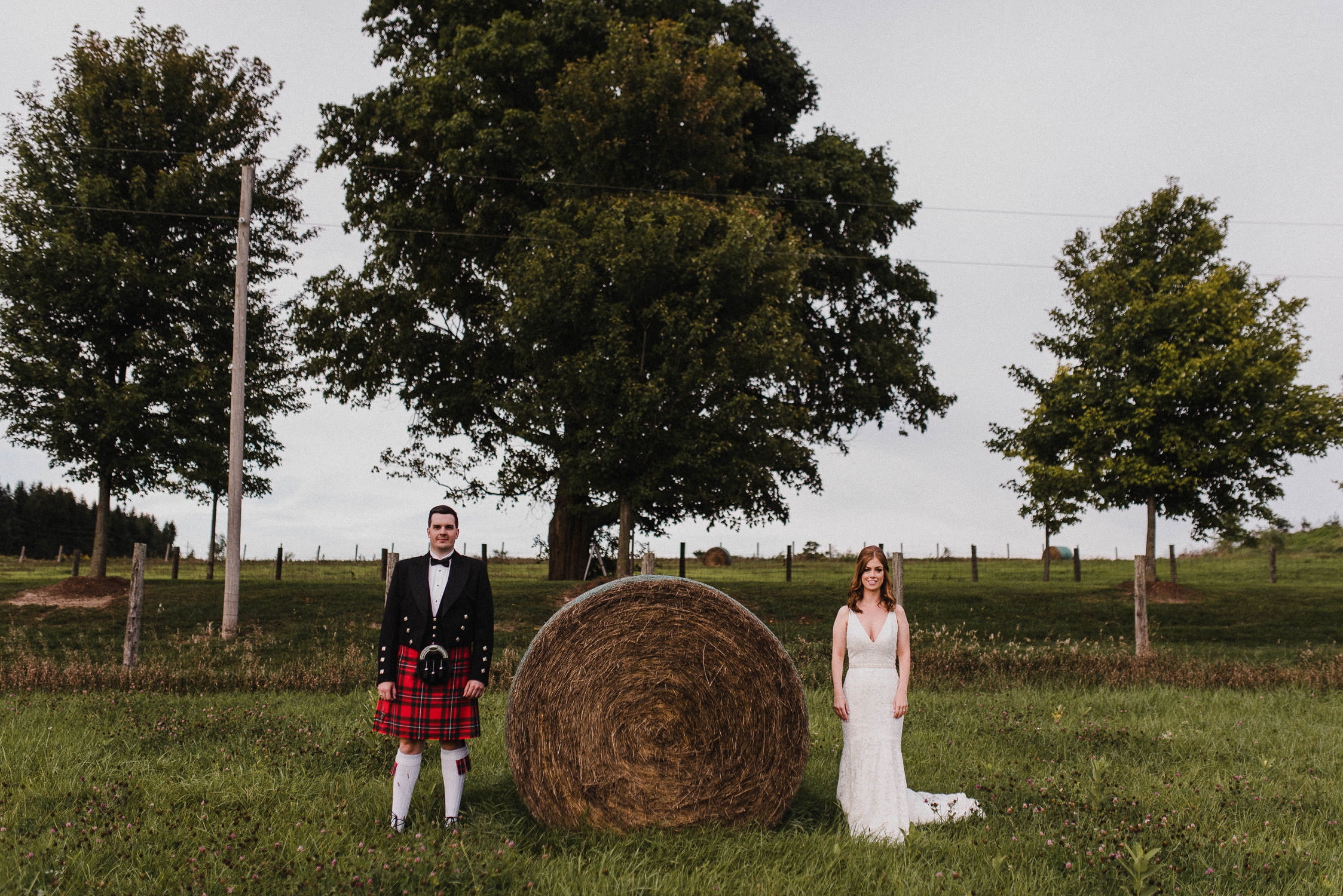 The bride and groom pose beside a haystack on the farm after their wedding ceremony at Cambium Farm.