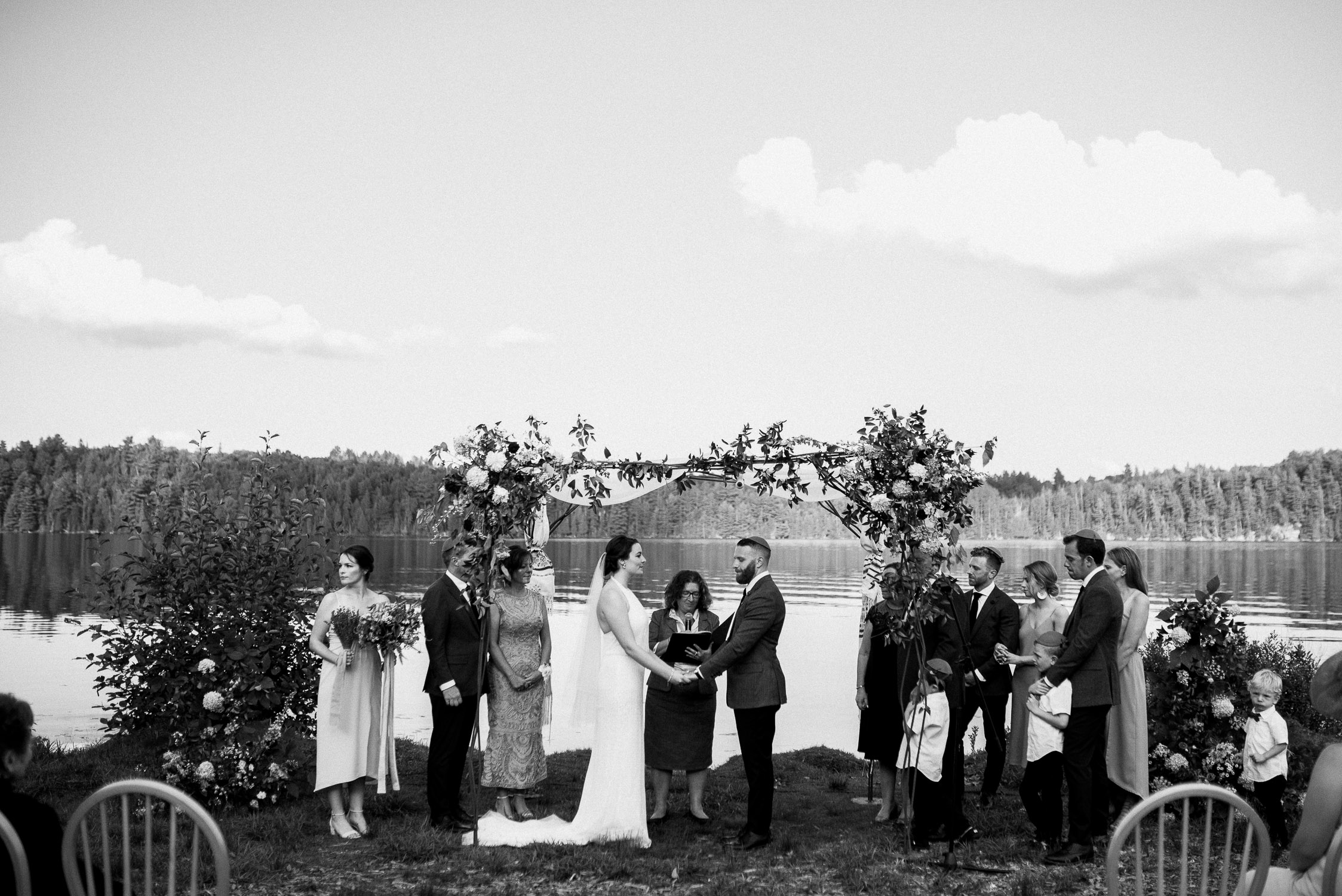 Black and white photo of the bride and groom holding hands at the alter during their Arowhon Summer Camp wedding.