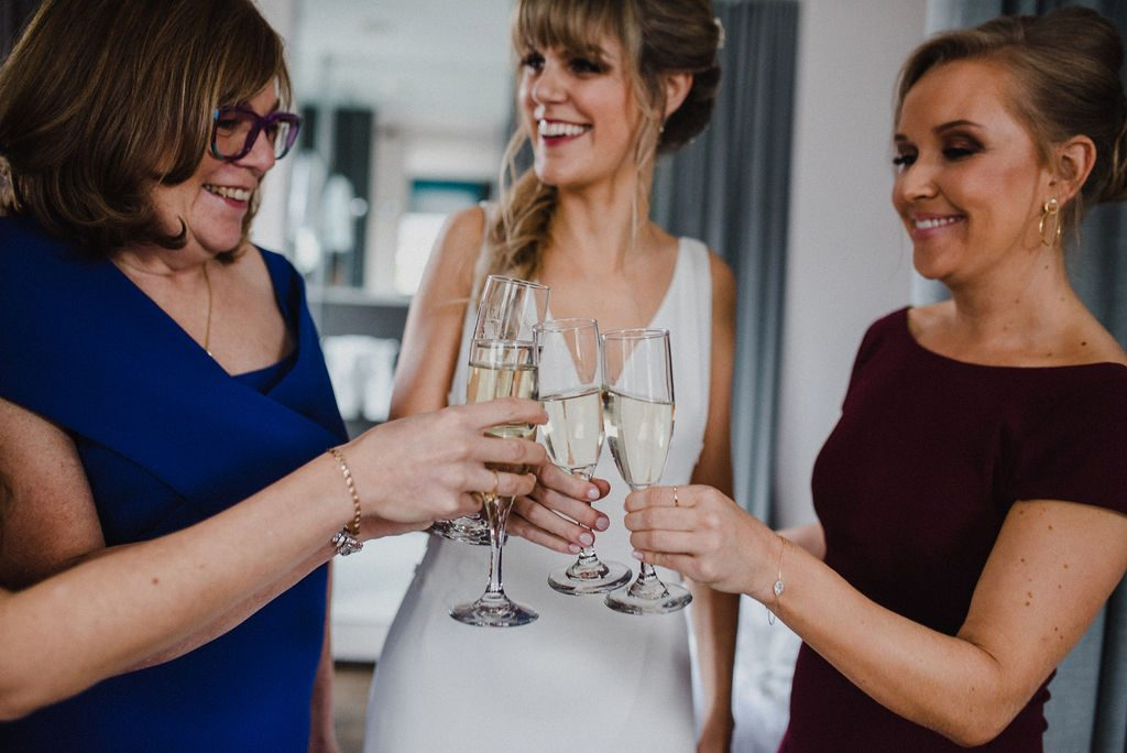 Bride cheering with mom and bridesmaid