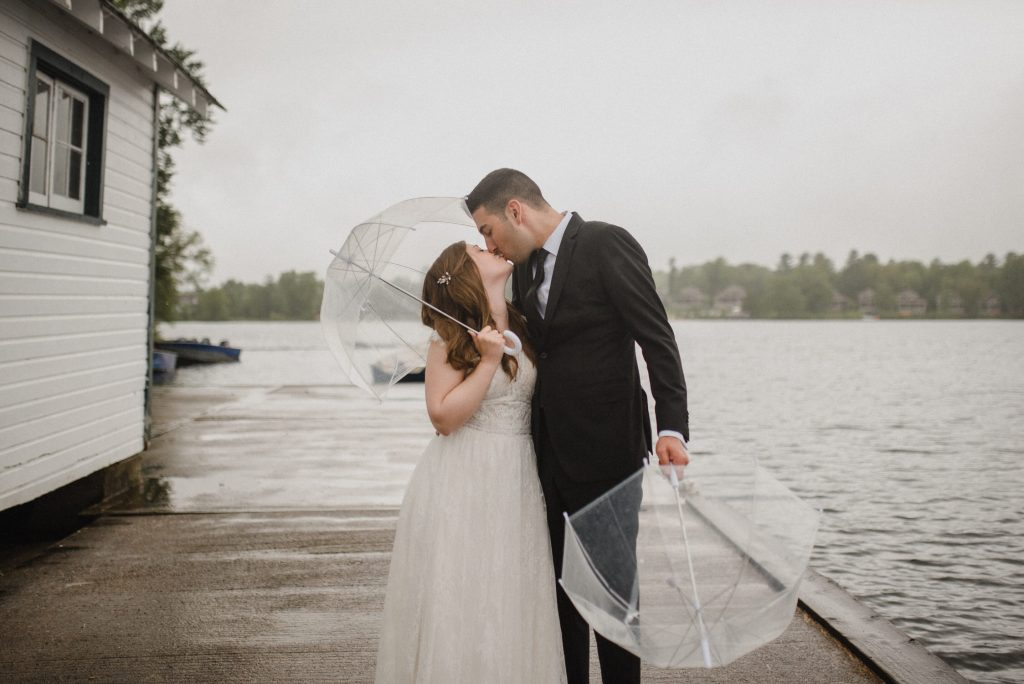 Bayview Wildwood Resort Wedding - bride and groom kiss in the rain with clear umbrellas