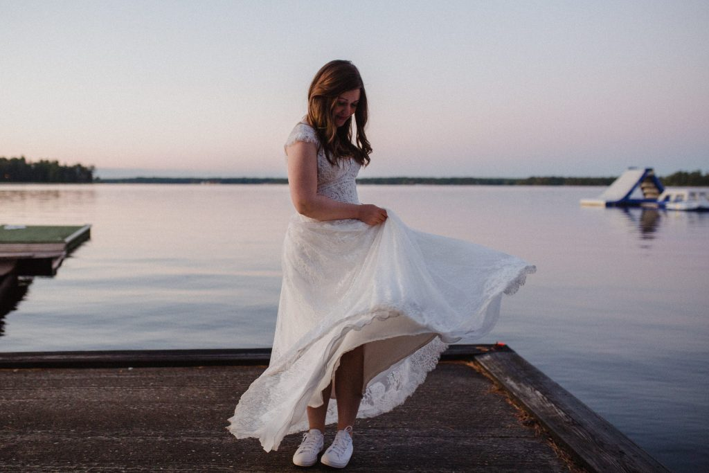 Bayview Wildwood Resort Wedding - bride dancing with dress by the water at twilight