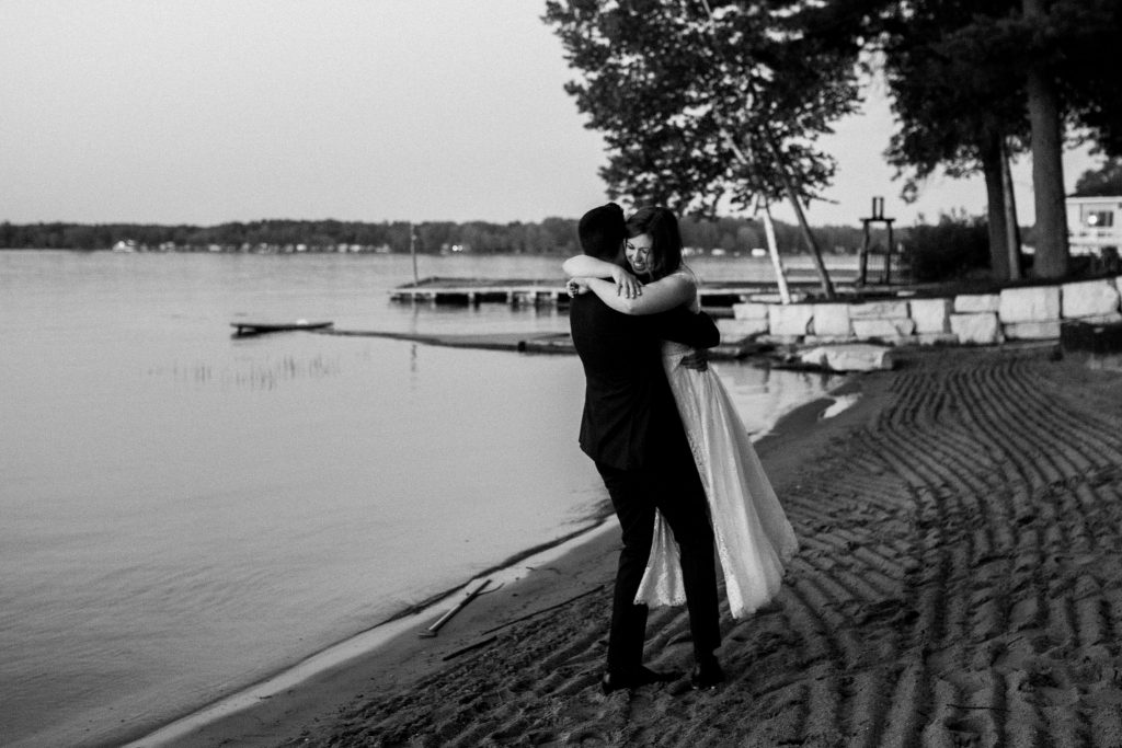 Bayview Wildwood Resort Wedding - groom swings bride in his arms on the beach