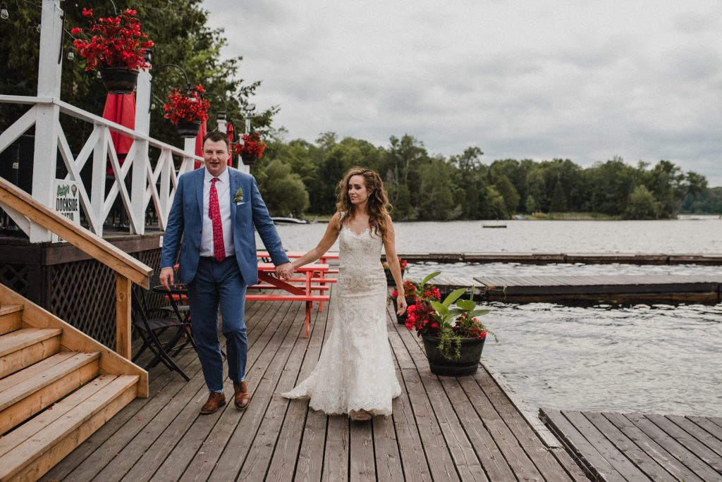 Bonnieview Inn Wedding - bride and groom walk hand in hand on windy dock