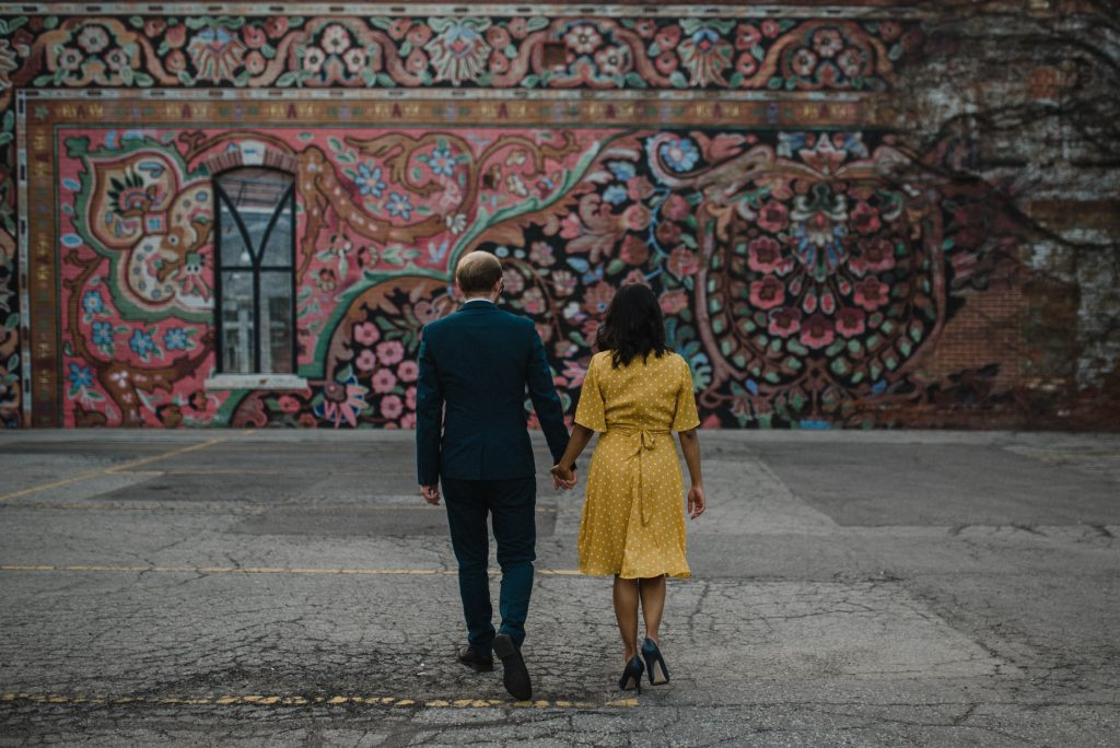 Liberty Village Engagement - couple holding hands in front of colourful mural