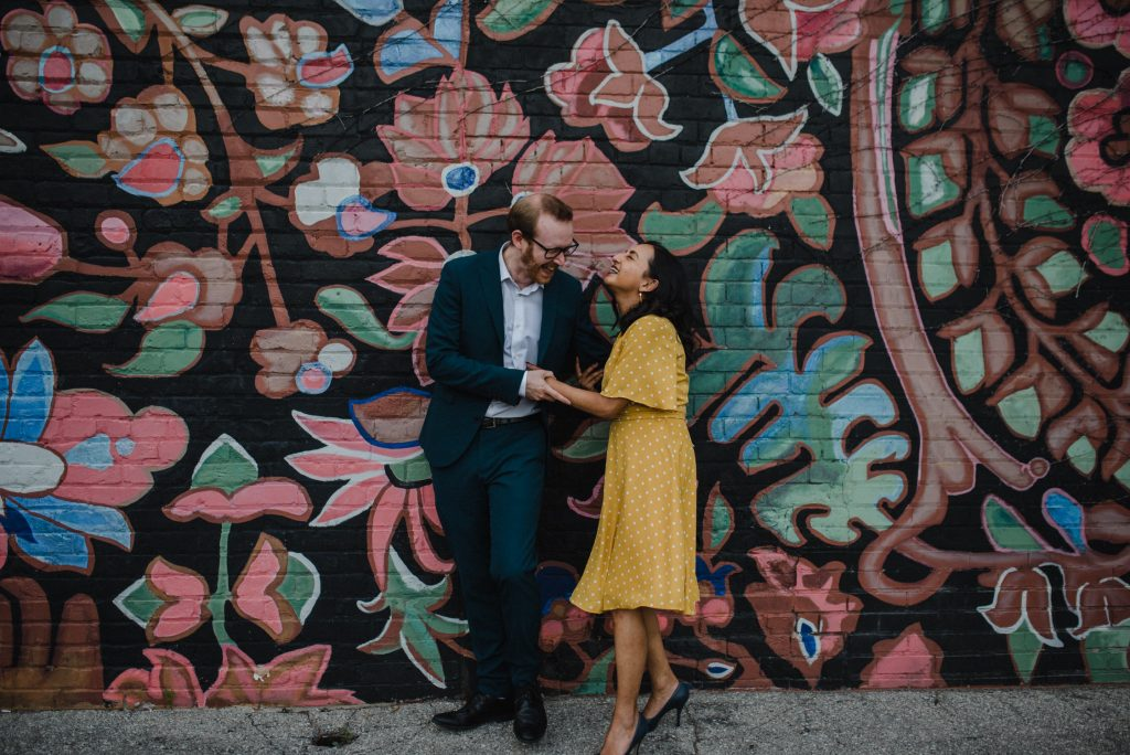 Liberty Village Engagement - couple being playful in front of mural