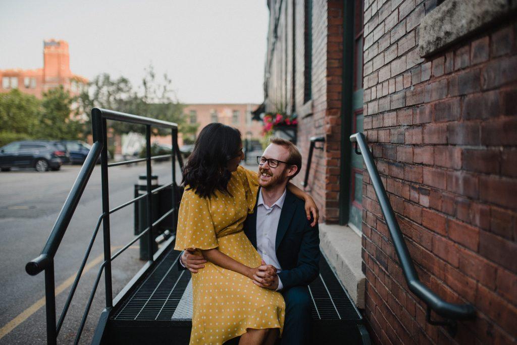 Liberty Village Engagement - Couple cuddle on steps