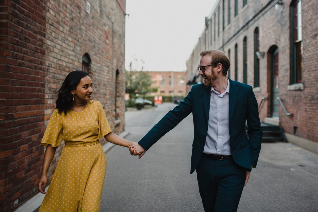 Liberty Village Engagement - couple hold hands walking in alleyway