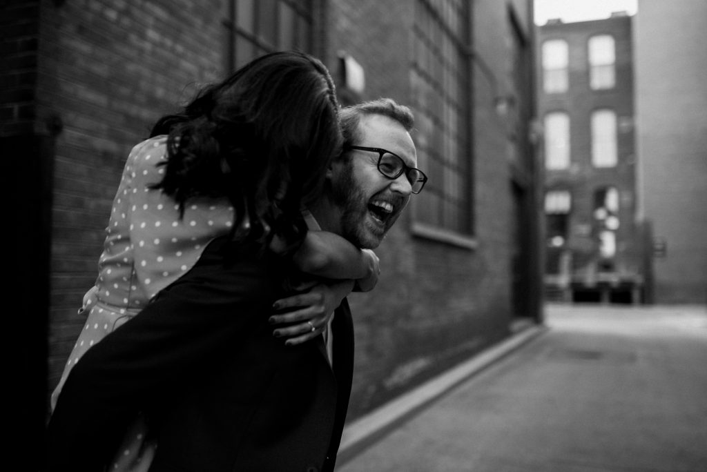 Liberty Village Engagement - couple horsing around in alleyway