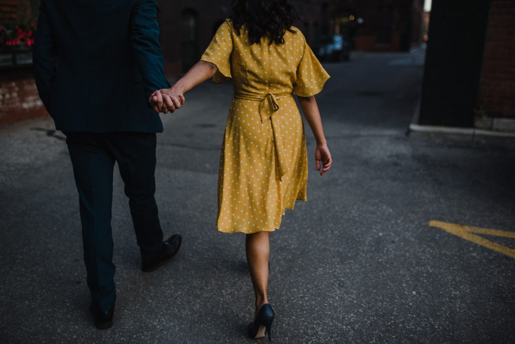 Liberty Village Engagement - couple walk hand in hand through alleyway