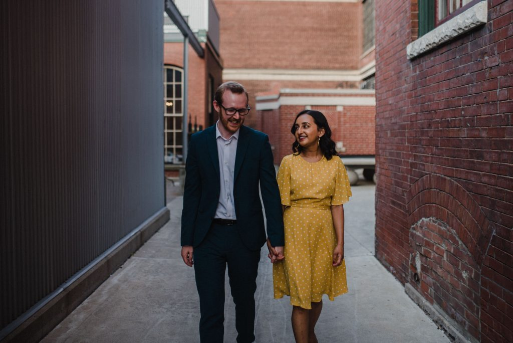 Liberty Village Engagement - couple walk together through alleyway