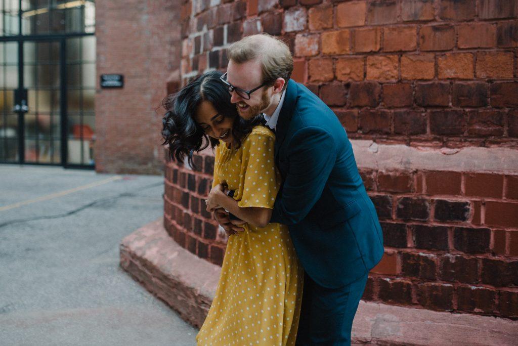 Liberty Village Engagement - couple embrace playfully near brick wall