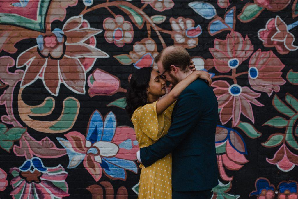 Liberty Village Engagement - couples share deep embrace near mural
