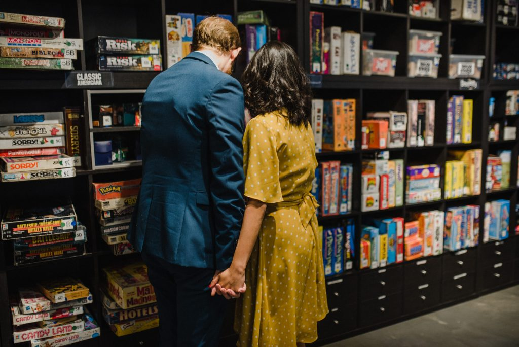 Snakes & Lattes Engagement - couple selecting from wall of games