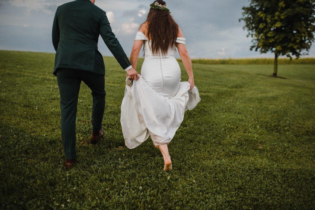 dyment's farm wedding - bride and groom walking barefoot through field