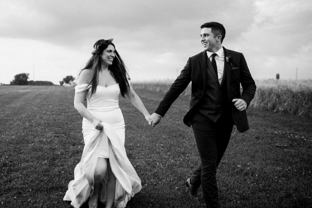 dyment's farm wedding - bride and groom running through field