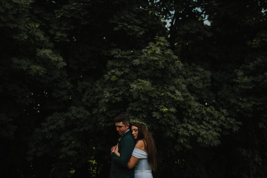 dyment's farm wedding - bride hugging groom near trees
