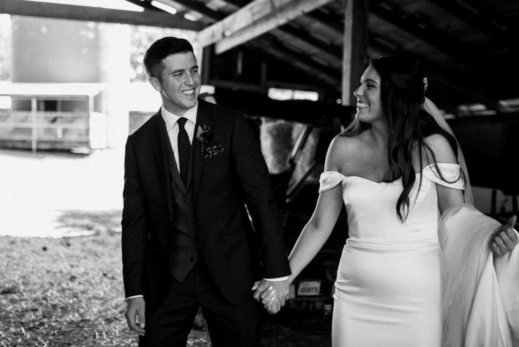 dyment's farm wedding - bride and groom playful inside barn