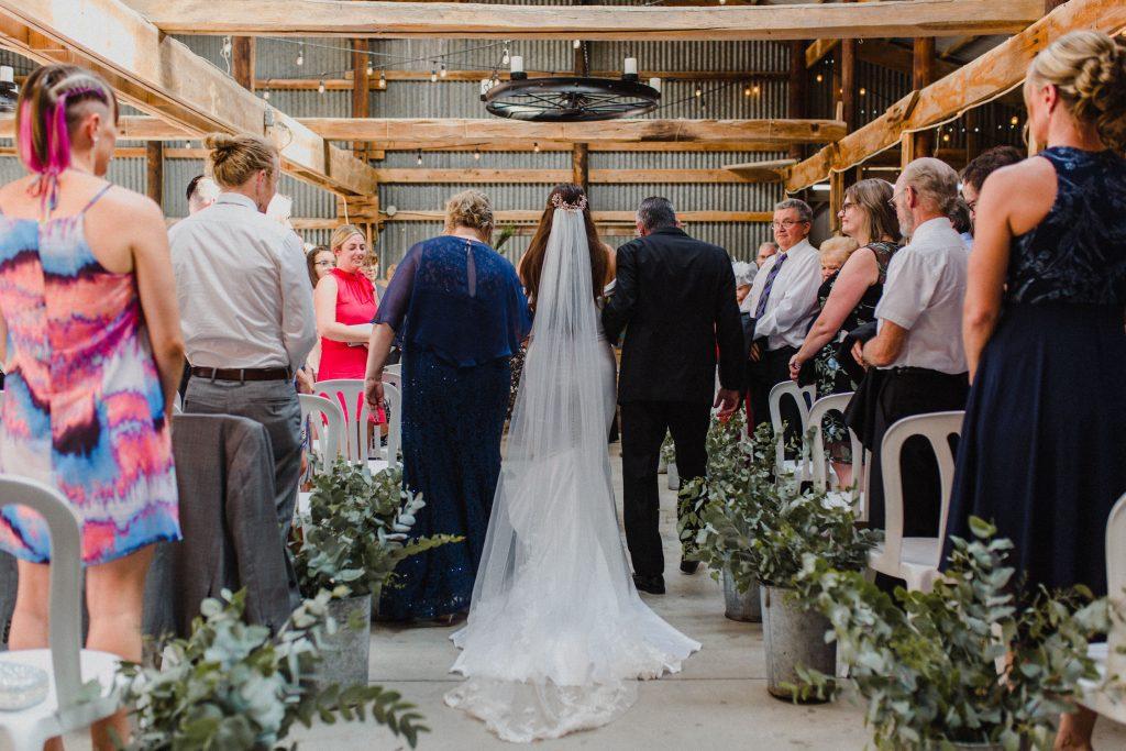 dyment's farm wedding - bride walking down aisle in barn