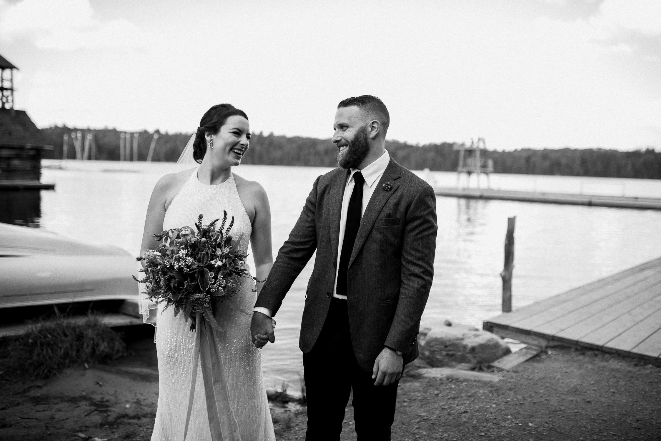 Black and white photo of the bride and groom holding hands in front of the lake at Arowhon Summer Camp.