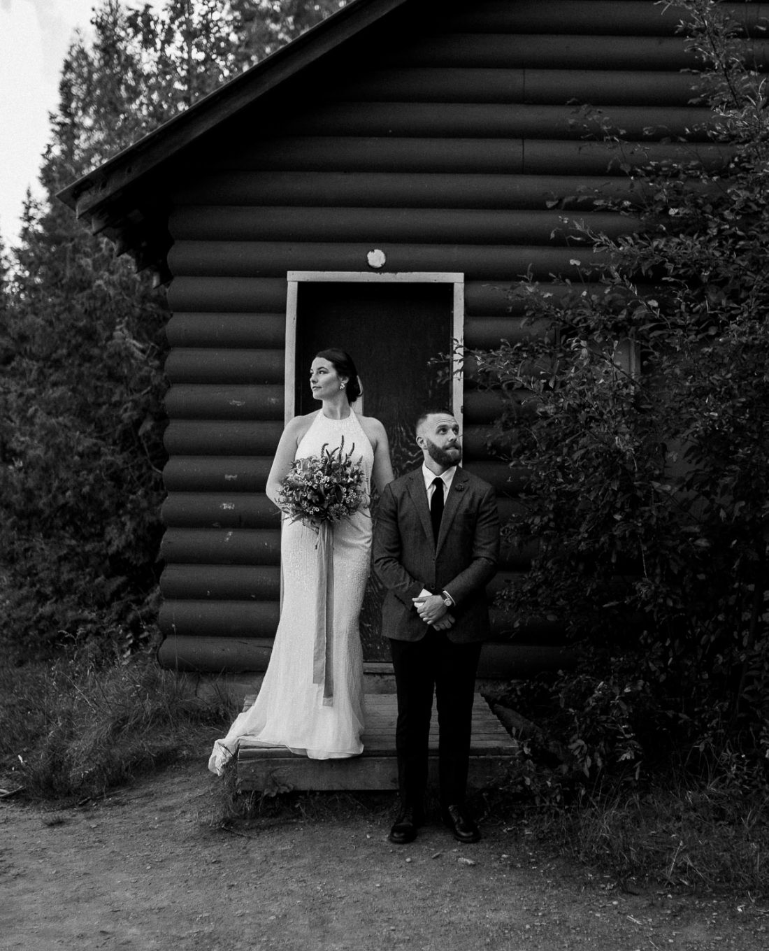 Black and white portrait of the bride and groom in front of a log cabin at their Arowhon Summer Camp wedding.