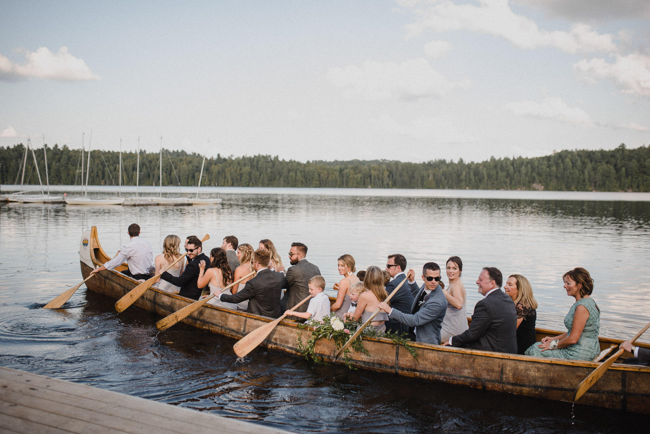 The wedding party takes a canoe to the wedding ceremony at Arowhon Summer Camp.