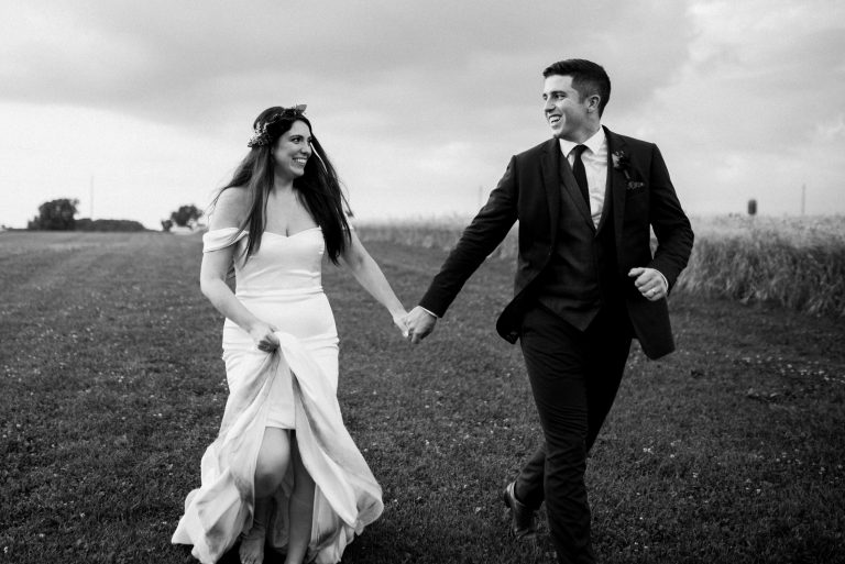 dyment's farm wedding - bride and groom running through field